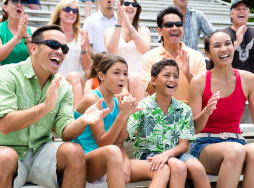 A family clapping and watching the dolphin lagoon show