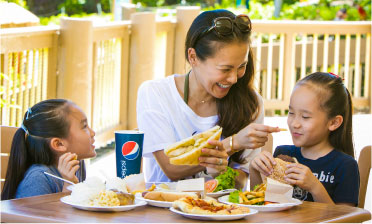 A mom and two daughters eating french fries and sandwiches