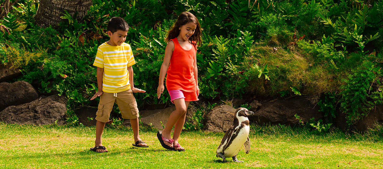 Boy and girl following penguin in lush park