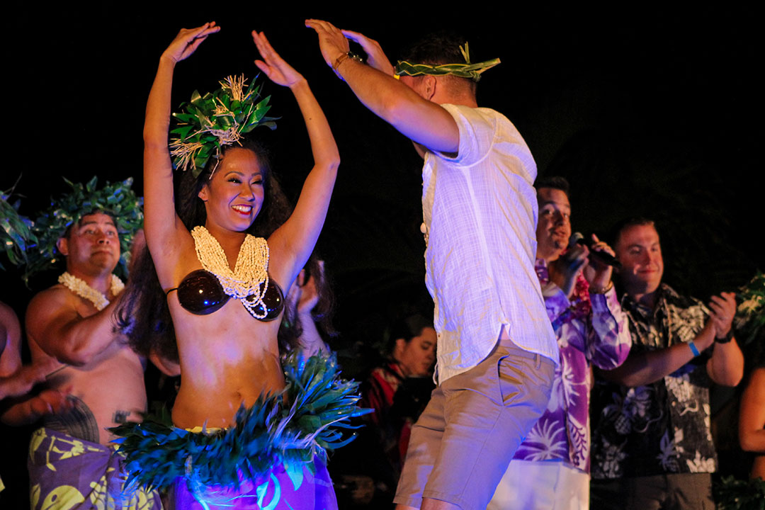Lu'au female hula dancer with guest on stage