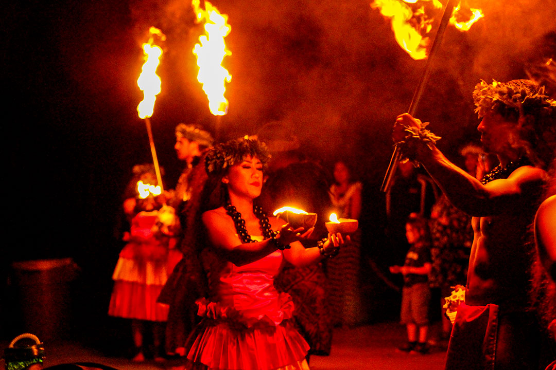 Opening scene of lu'au, the story of Pele, fire in hands of female dancers, males with torches