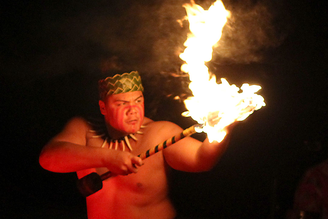 Male dancer with burning torch starting fire-knife dance